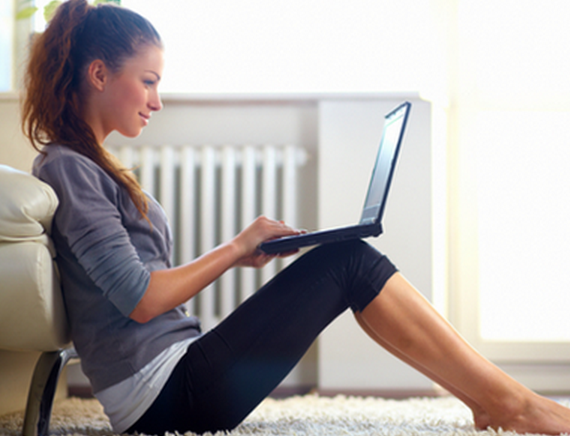 woman-sitting-on-laptop-in-workout-clothes